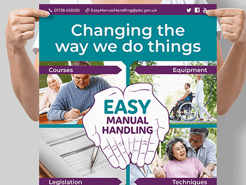 Image shows a woman holding an A1 poster advertising Perth and Kinross Council's Learning and Development Team's Easy Manual Handling website